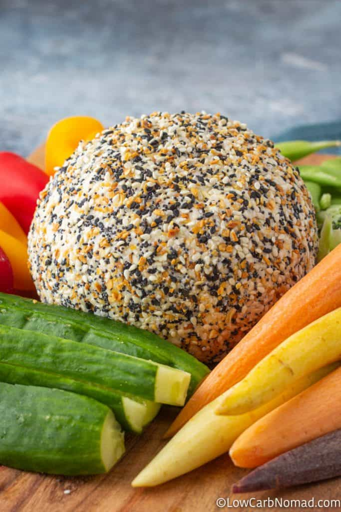 Cheese ball on a platter with carrots, cucumbers, peppers and sugar snap peas