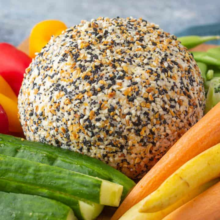 Everything bagel cheese ball on a platter with carrots and peppers