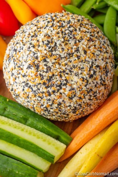 Everything bagel Cheese ball on a platter with carrots, cucumbers, peppers and sugar snap peas