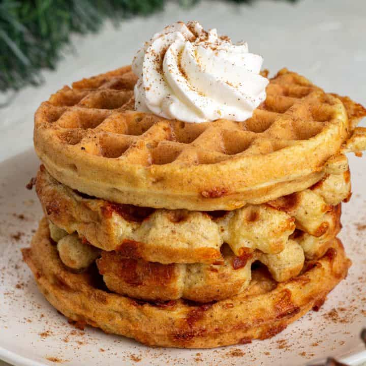 Gingerbread Chaffles on a white plate topped with keto whipped cream.