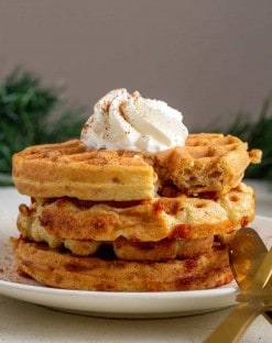 3 gingerbread chaffles on a white plate with a dolp of whipped cream on top