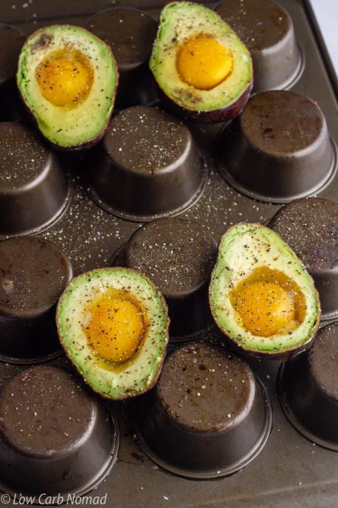 avocados with eggs on an upside down muffin pan to bake in the oven