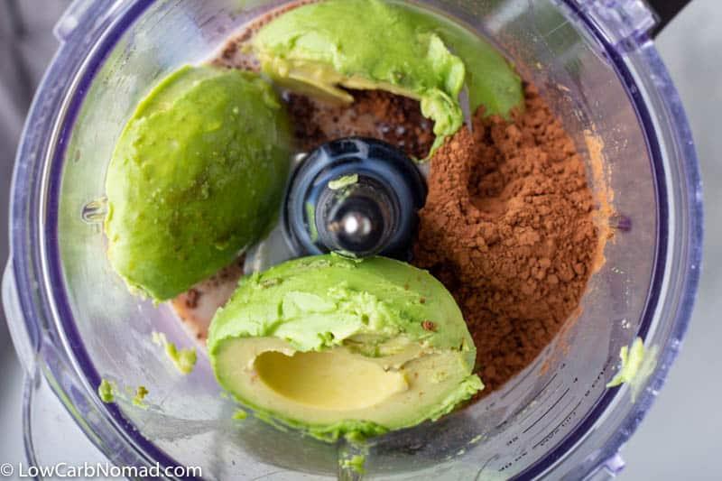 Avocado, cocoa powder, sweetener and coconut milk in a food processor to make keto avocado chocolate pudding