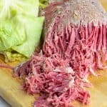 Crockpot corned beef and cabbage on a wooden cutting board ready to be served