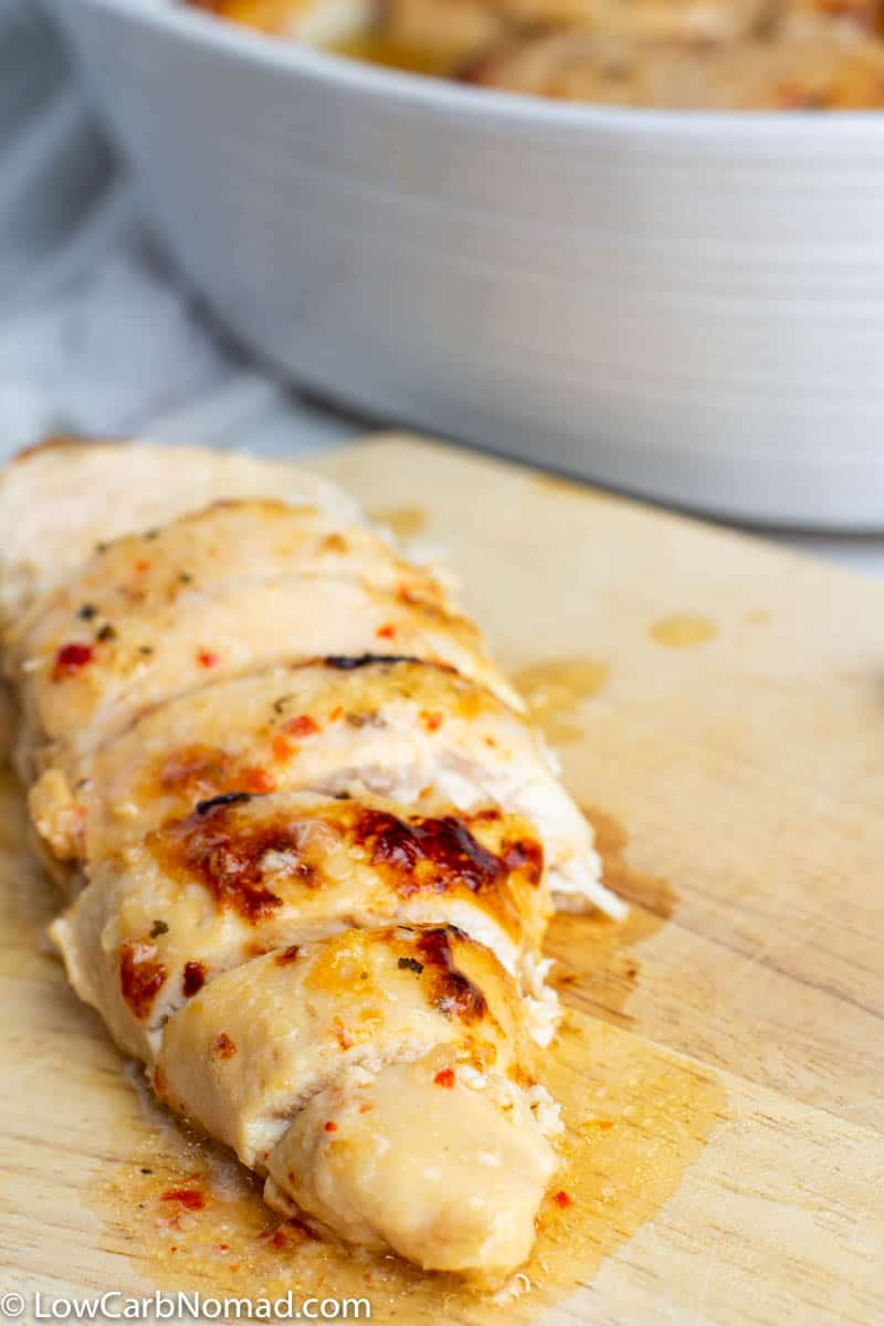 Baked Italian Chicken cooked on sliced on a cutting board