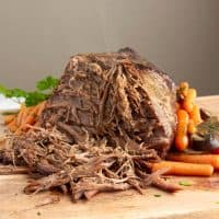 Instant Pot Pot Roast with veggies being sliced on a butcher block
