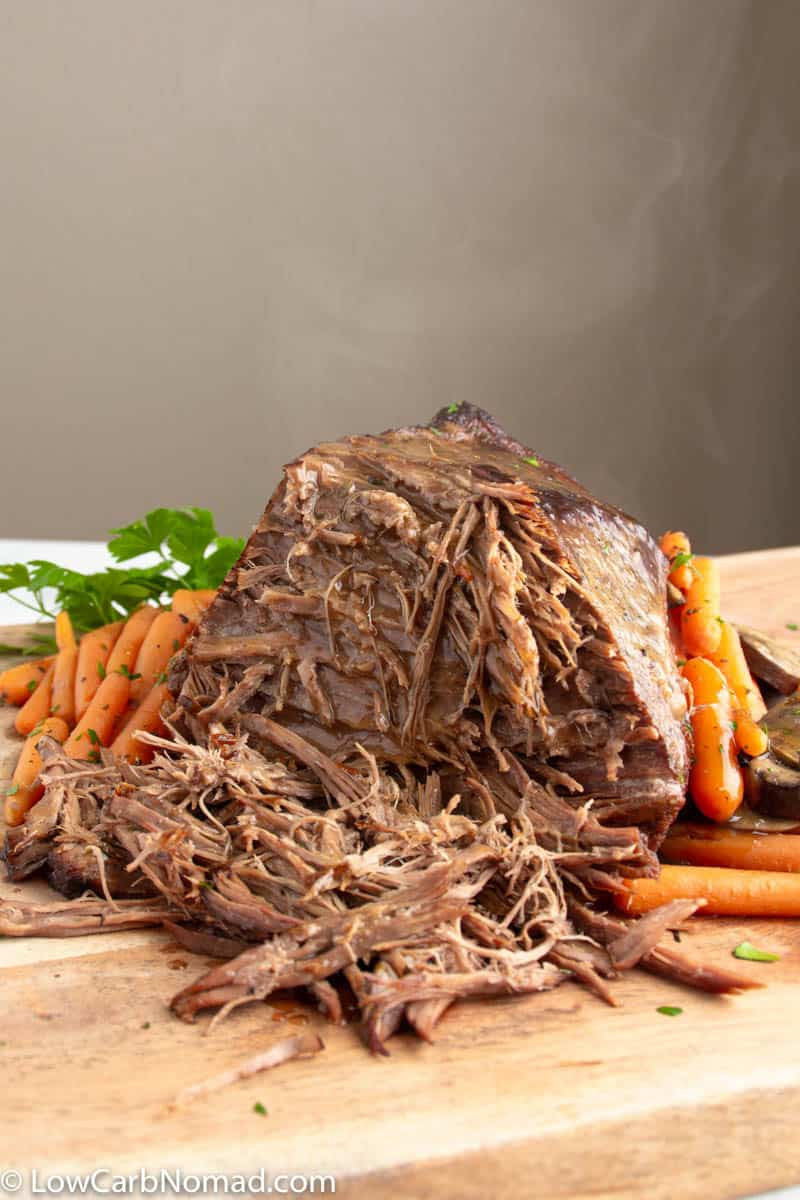 Low carb pot roast recipe on a butcher block with veggies
