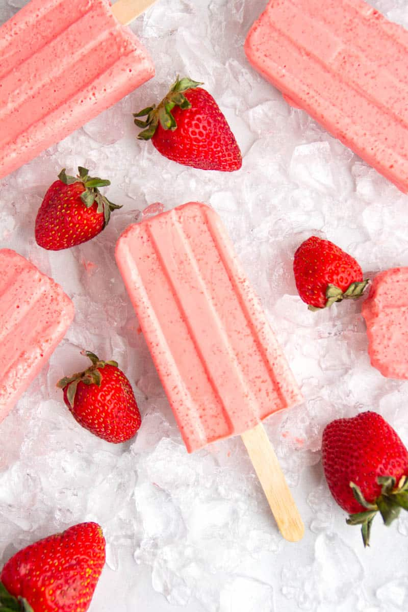 Keto Strawberry Popsicles laying on ice with a few strawberries