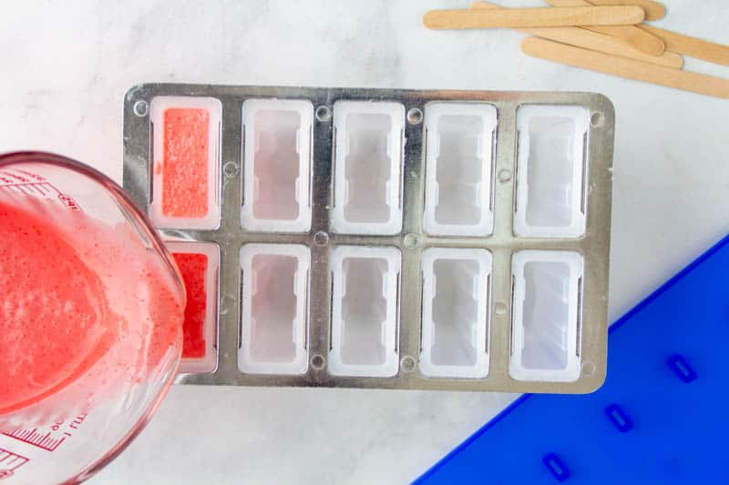 keto popsicle mixture being poured into popsicle mold