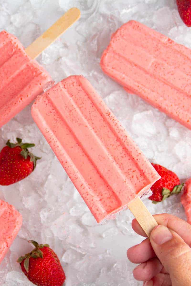 Hand holding a strawberry keto popsicle
