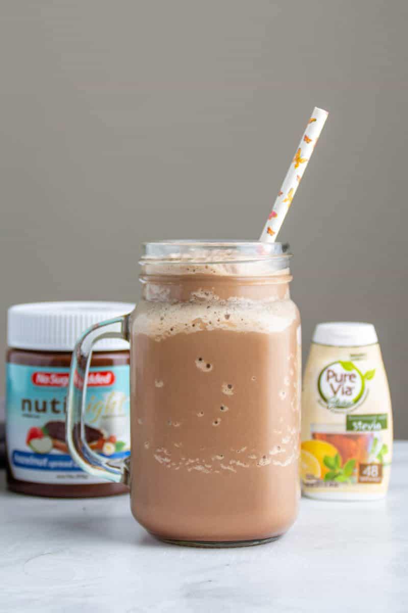 keto milkshake in a glass with a straw