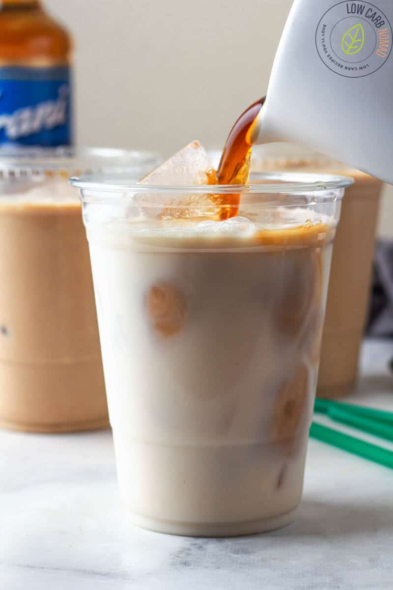 pouring iced coffee into cup