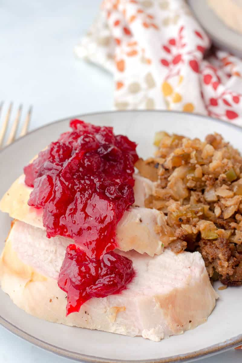 keto cranberry sauce poured on top of fresh made turkey and keto stuffing on a plate