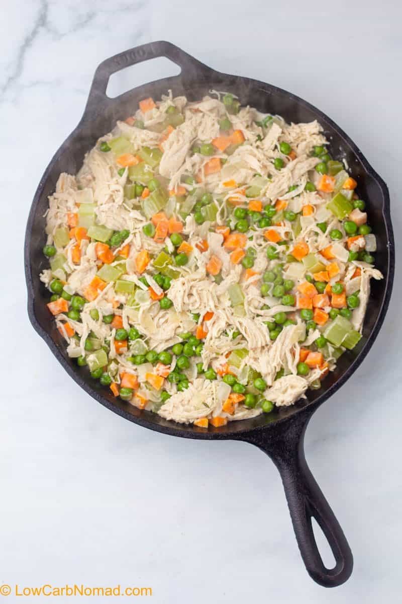 chicken and veggies in cream sauce in a cast iron skillet