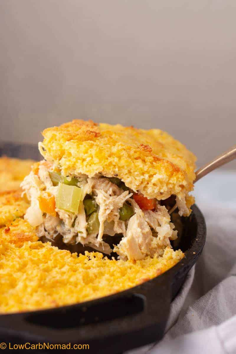 Low Carb Keto Chicken Pot Pie being scooped out of a cast iron skillet