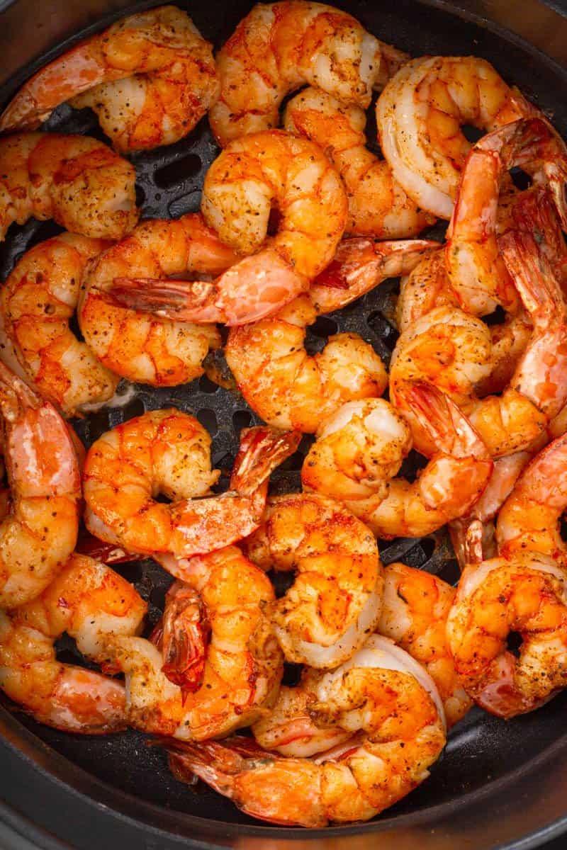 Shrimp coated in cajun seasoning in the basket of aan air fryer