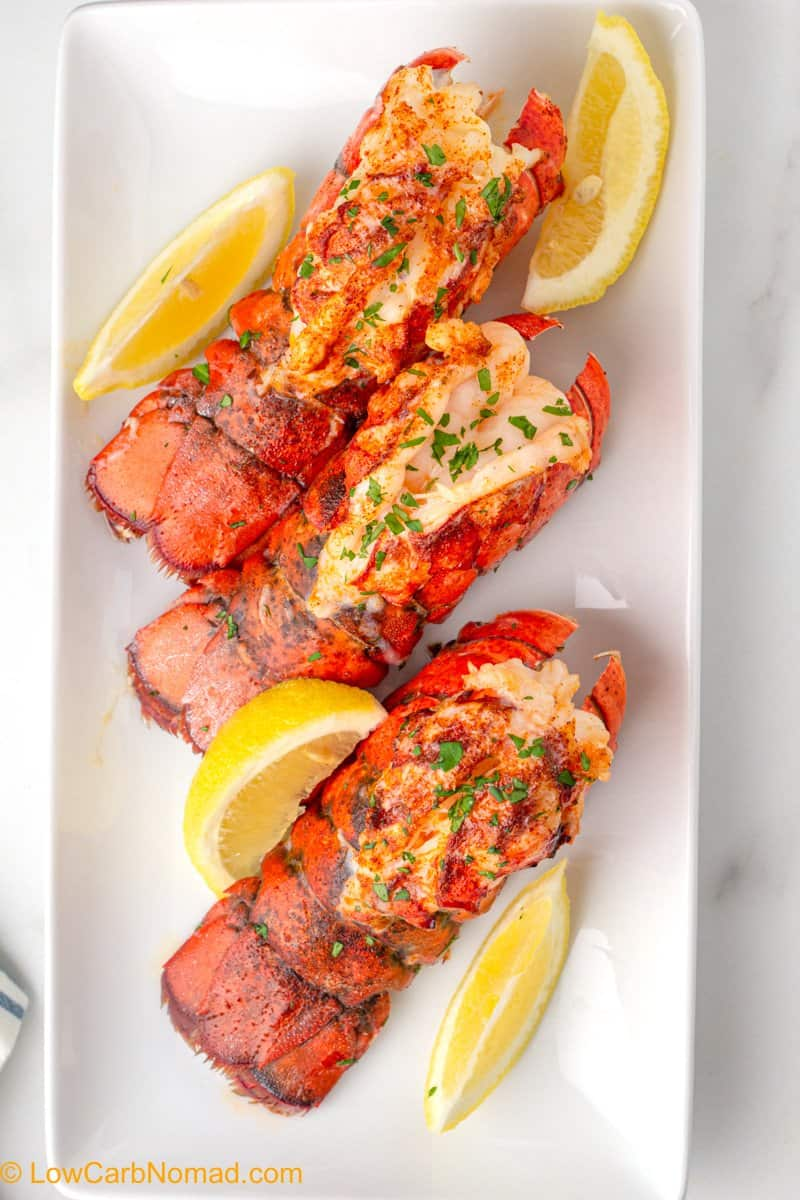 3 cooked lobster tails on a white plate