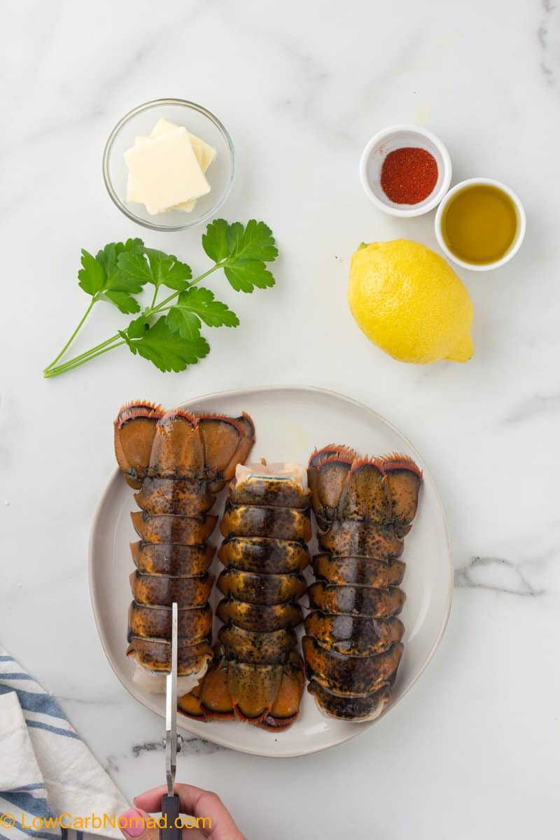 Cutting the shell of an uncooked lobster tail with kitchen shears