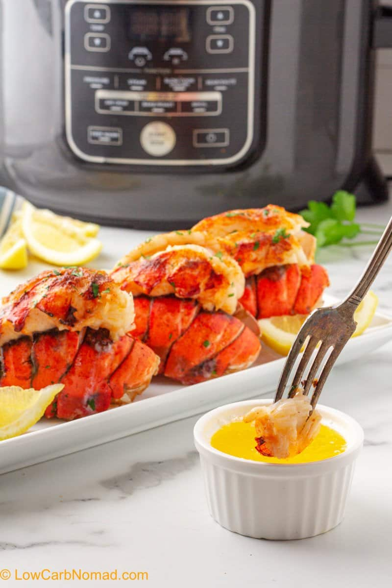 bite of lobster tail being dipped into melted butter