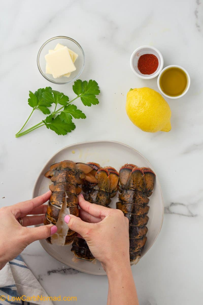 2 hands separating the lobster shell